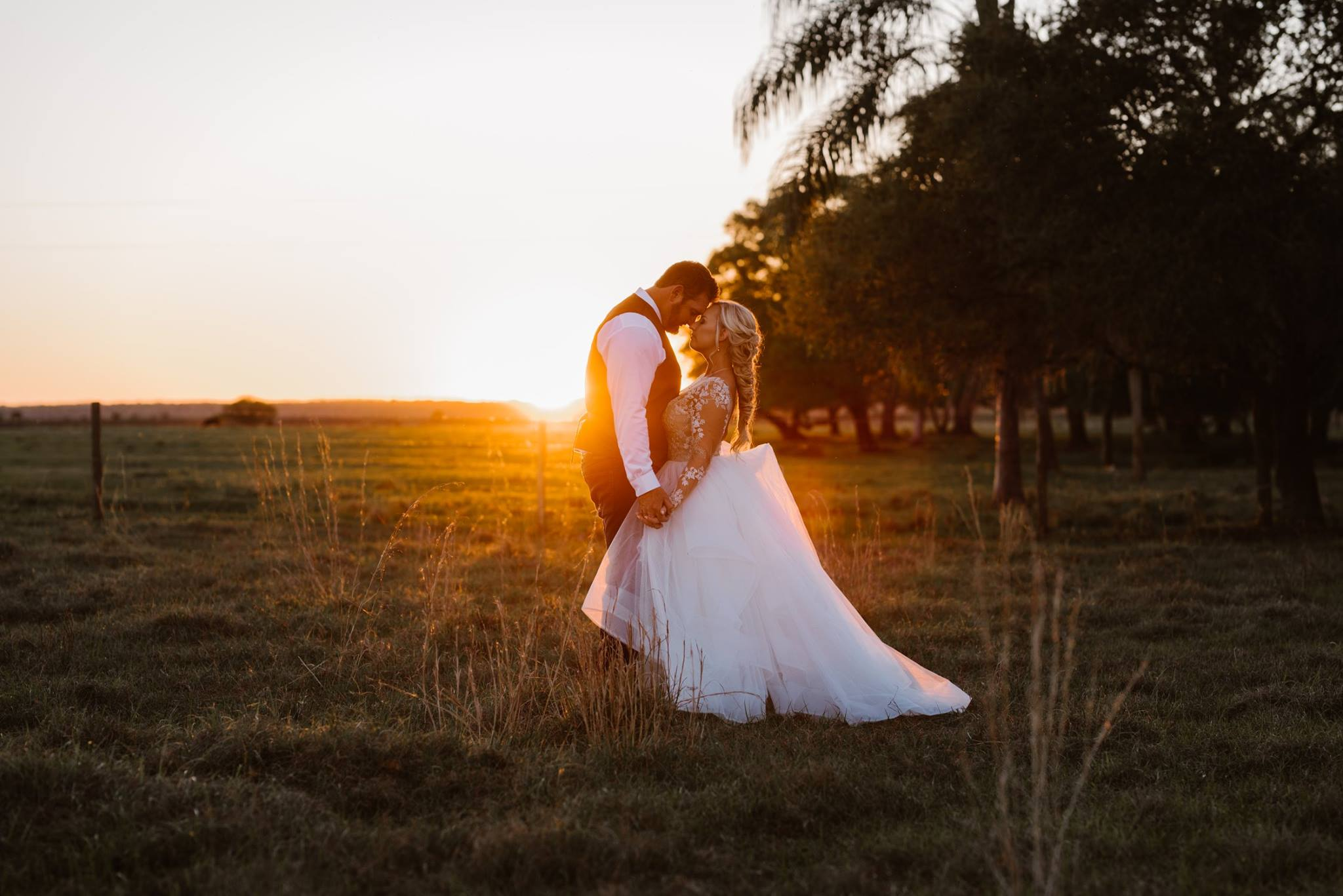 Newly married couple kissing in the field