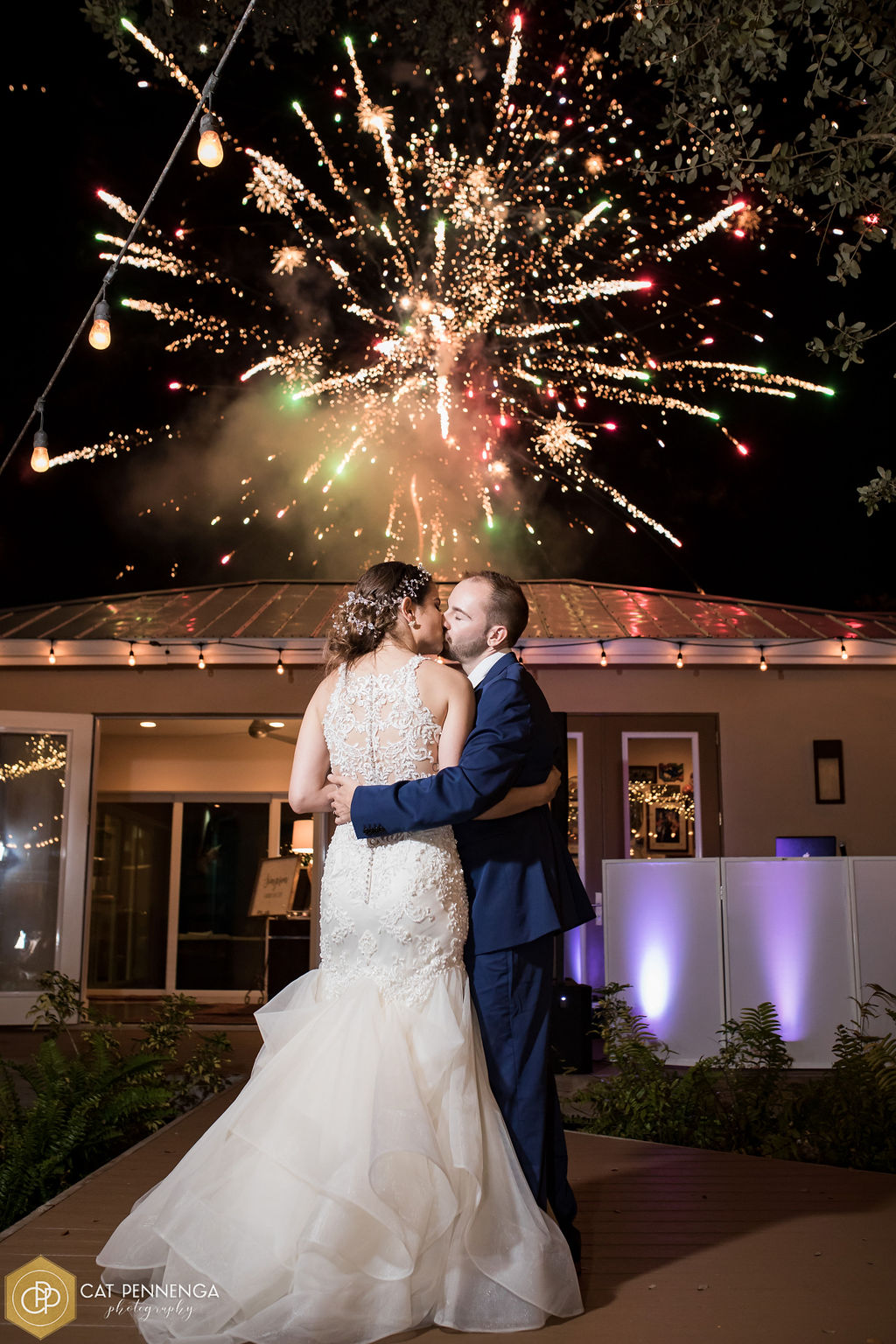 Newly married couple kissing with fireworks in the background