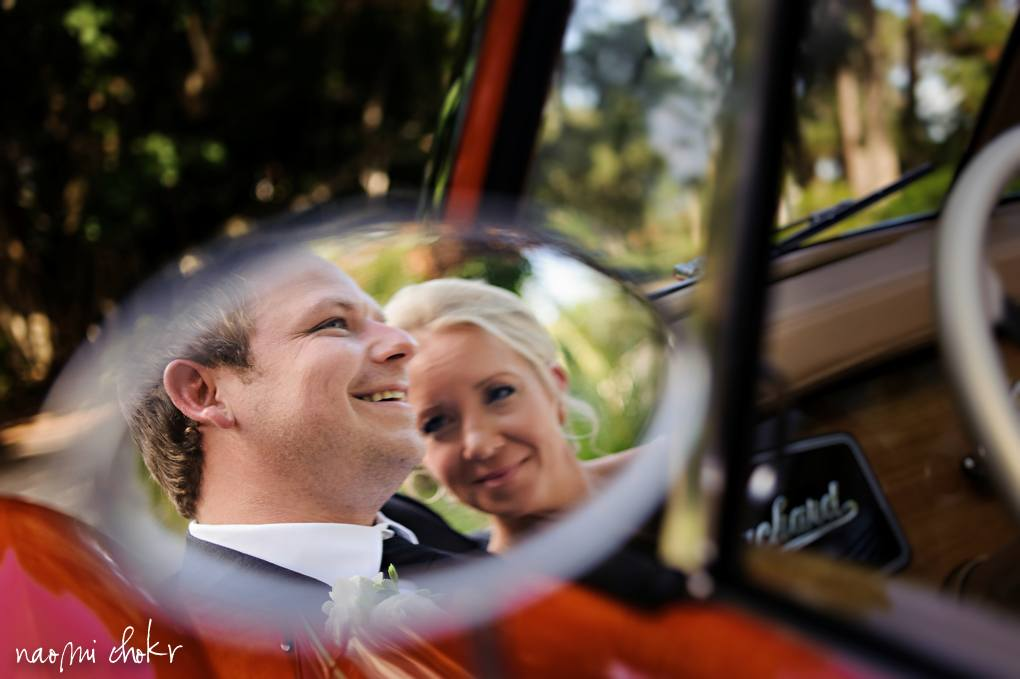 Reflection of a newly married couple in a car mirror
